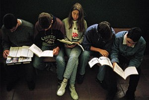 Young people studying Five young people study sat down in a bank of a corridor of the Santamarca Institute of High school. Madrid